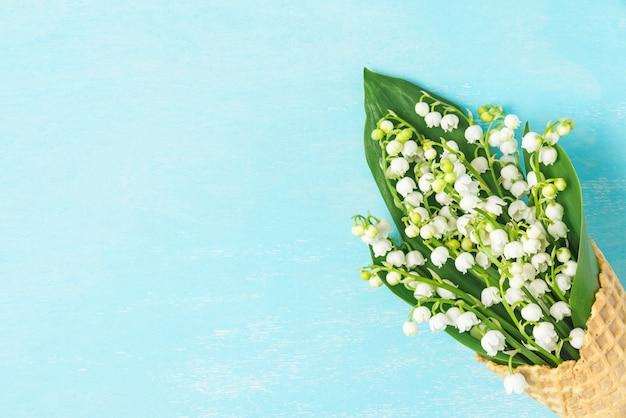 Frühlingslilie des tals blüht im waffelkegel. minimales federkonzept. flach liegen. draufsicht