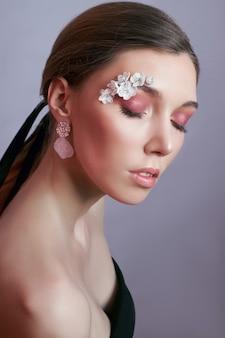 Frühlingsmake-up-augenfrau mit weißen blumen. kreatives blumenschönheits-augen-make-up. wimpernkosmetik mit sommerblumen