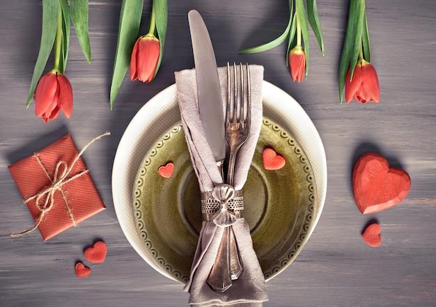 Frühlingsmenükonzept mit frischen tulpen und herzdekoration auf rustikalem holz