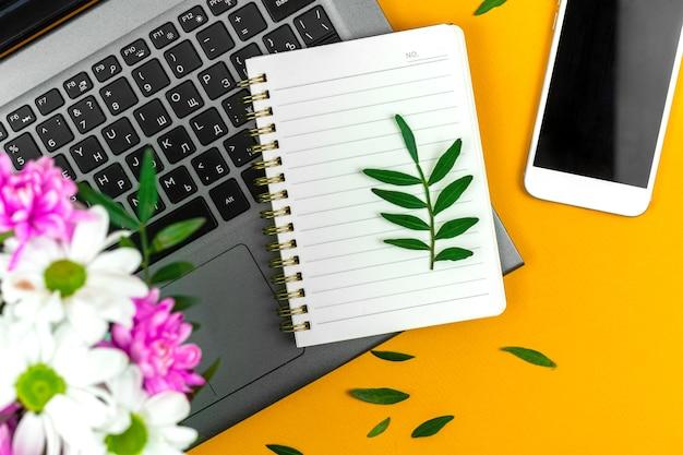 Frühlingsmodell mit leerem notizblock, bürodesktop mit blumenstrauß, feiertagshintergrundfoto