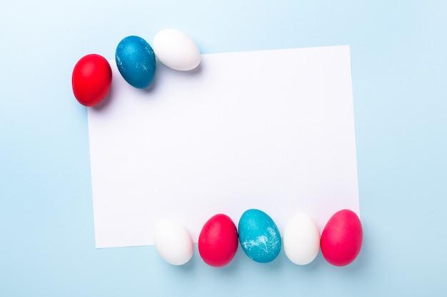 Frühlingsmodell mit ostereiern und rohling des weißen papiers auf blauem hintergrund. osterkonzept. speicherplatz kopieren. draufsicht