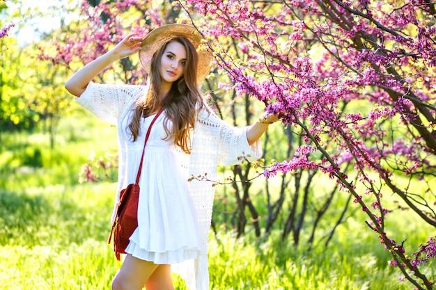 Frühlingsmodeporträt des eleganten modells, das am blühenden sakura-park aufwirft, genießen sonnigen warmen tag