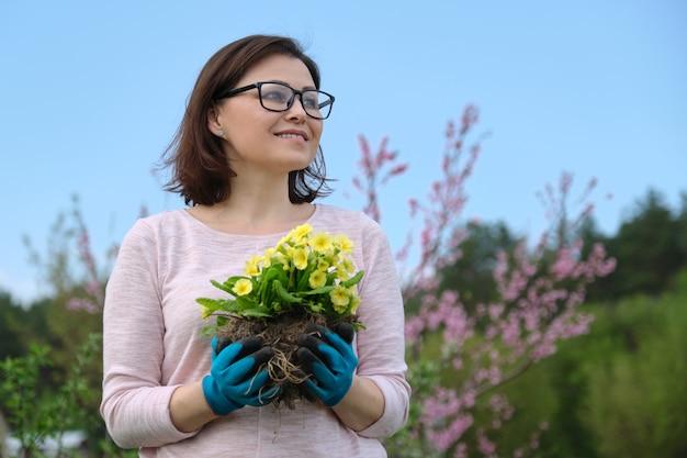 Frühlingsporträt der frau mittleren alters in handschuhen mit gelben primelblüten