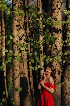 Frühlingsporträt eines lachenden mädchens in einem langen roten kleid mit langen haaren, die im park im wald gehen