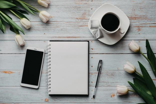 Frühlingsrohlinge des arbeitsplatzes eines freiberuflers mit einem blumenstrauß von weißen tulpen, einem smartphone, einem leeren weißen blumenstrauß und einem tasse kaffee