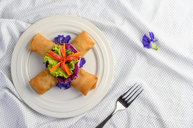 Frühlingsrolle oder gebratene frühlingsrollen auf dem weißen teller thailändisches essen. draufsicht.