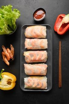 Frühlingsrollen des asiatischen essens mit gemüse, garnelen im reispapier auf schwarzem hintergrund. von oben betrachten. vertikale ausrichtung.