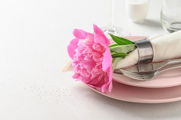Frühlingsromantische tabelleneinstellung mit rosa pfingstrosenblumen auf einem weißen tisch. nahansicht.