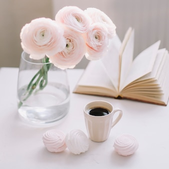 Frühlingsromantisches stillleben mit blumen, kaffeetasse, buch und marshmallows