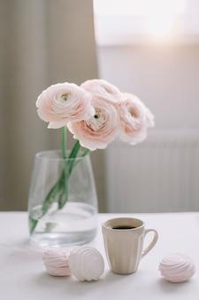 Frühlingsromantisches stillleben mit blumen, kaffeetasse und marshmallow