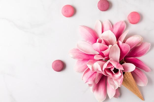 Frühlingsrosa magnolienblüten im waffelkegel mit makronen. frühlingskonzept. flach liegen. draufsicht