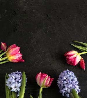 Frühlingsrosa tulpen und lila hyazinthe auf tafel