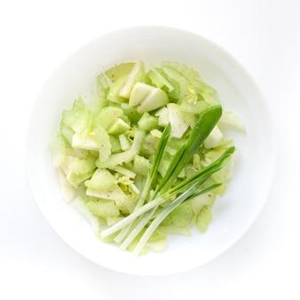 Frühlingssalat mit sellerieapfel und -grüns in einer weißen platte, draufsicht, diät