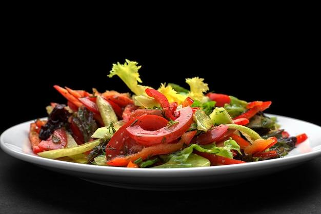 Frühlingssalat von frischem gemüse, gurken, tomaten, salat, paprika auf einem weißen teller, auf einem dunklen hintergrund