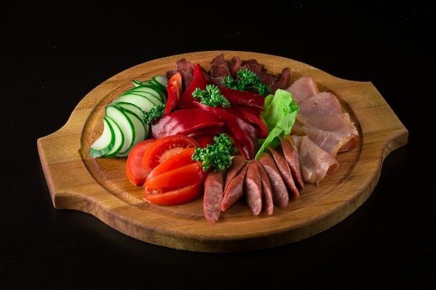Frühlingsschnitt aus geräuchertem schinken, frischen tomaten, gurken, rotem pfeffer