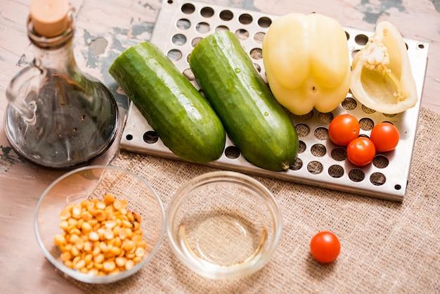 Frühlingssommer-diätsalat mit erdbeeren, gurke, grünem feldsalat und jogurtminzensoße diente in der blauen platte mit stoffserviette über grauem beschaffenheitshintergrund. draufsicht, kopie, raum