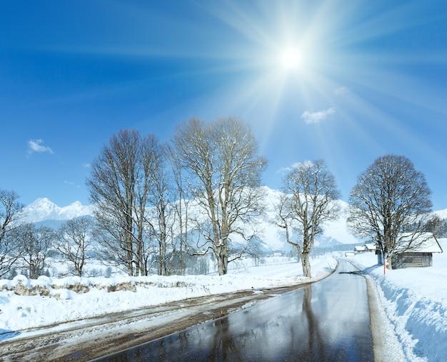 Frühlingssonne und straße durch das bergdorf in österreich mit reflexion von bäumen im auftauenden schnee.