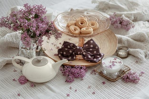 Frühlingsstilleben mit lila blumen, süßigkeiten, milch und dekorationsdetails