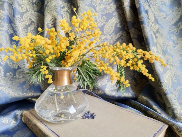 Frühlingsstilleben mit mimosen in einer vase und einem alten goldrahmen mit einem stoffvorhang