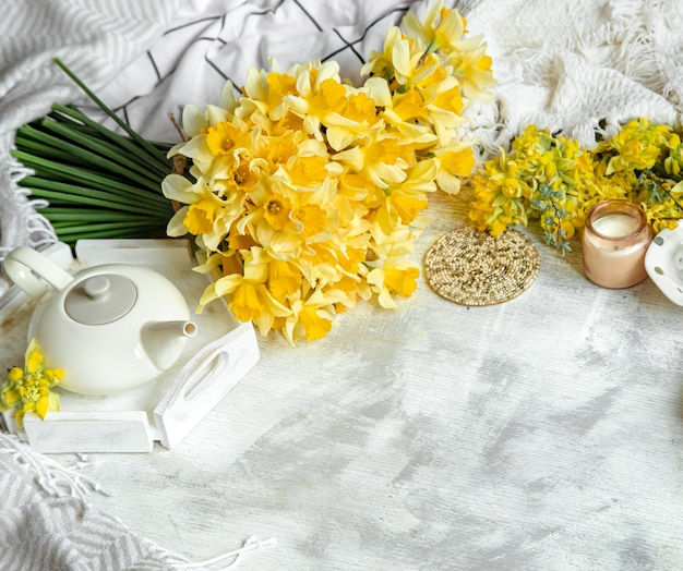 Frühlingsstillleben mit einer tasse tee und blumen. heller hintergrund, blühendes und gemütliches haus.