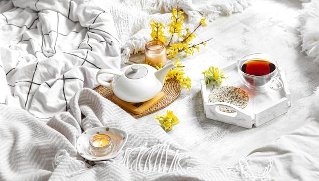 Frühlingsstillleben mit einer tasse tee und blumen. leuchttisch, blühendes und gemütliches haus.