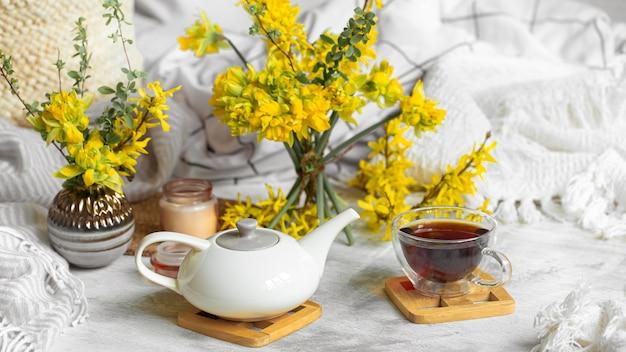 Frühlingsstillleben mit einer tasse tee und blumen