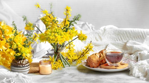 Frühlingsstillleben mit einer tasse tee und blumen.
