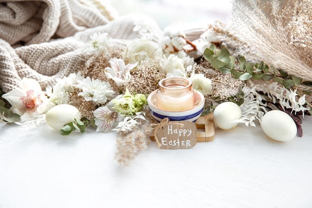 Frühlingsstillleben mit ostereiern, kerzen in einem anhänger und blumen gegen dekor details. osterferienkonzept.
