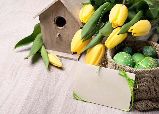 Frühlingsstilllebendekorationen mit vogelhaus, gelben tulpen, ostereiern, textraum auf papierkarte