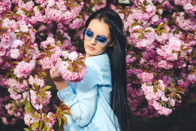 Frühlingstag. schönes mädchen in gläsern. modische frau in trendigen brillen. frühlingsrosa sakura-blüte. weibliche frühlingsmode.