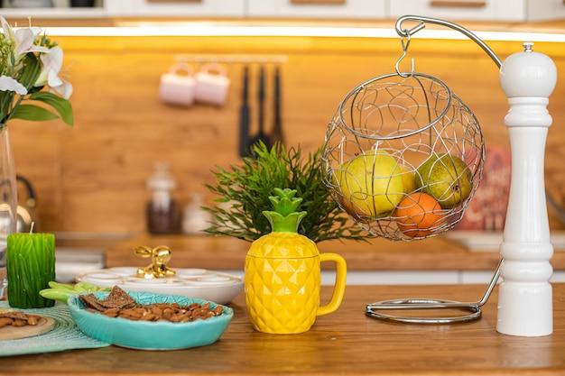 Frühlingstheke mit frischem obst, mandel in platte und ananas-teekanne, blumen in vase, kerze, obst in rundem kleiderbügel und pfeffermühle.