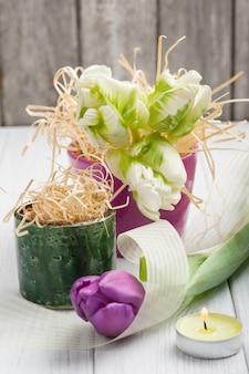 Frühlingstischschmuck mit tulpen und brennender kerze