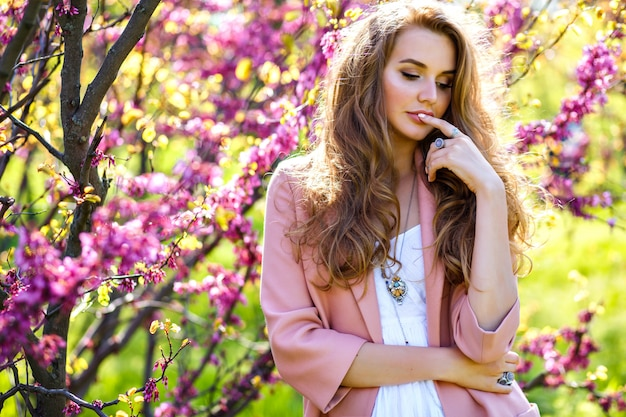 Frühlingstrends porträt der eleganten prächtigen schönen stilvollen frau, die nahe blühenden bäumen am stadtgarten aufwirft