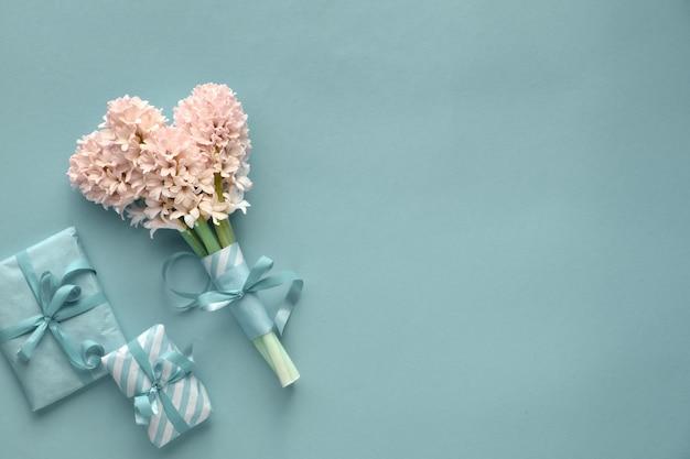 Frühlingstürkis mit der hyazinthe und geschenkboxen eingewickelt im gestreiften papier auf papierhintergrund mit kopieraum