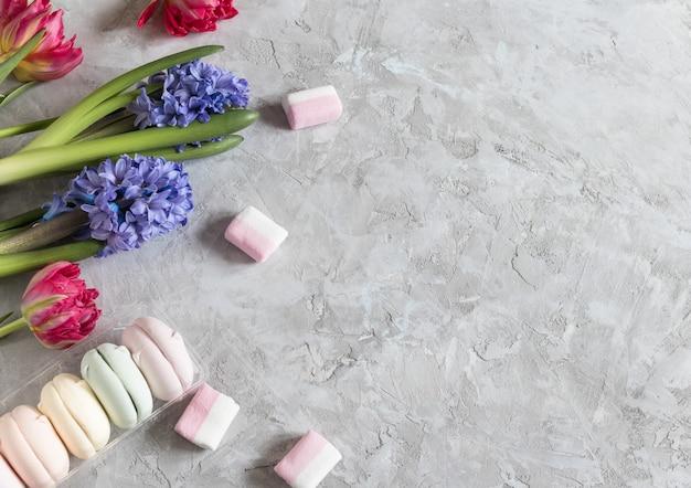 Frühlingstulpe und hyazinthe mit mulmarshmallows und bändern auf grauem hintergrund