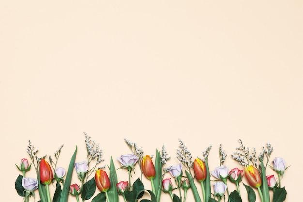 Frühlingstulpen u. rosen auf dem gelben hintergrund
