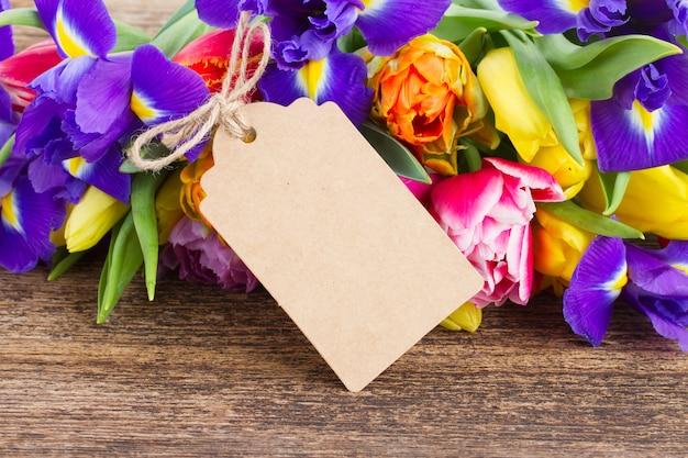 Frühlingstulpen und iris mit papieranhänger auf holz