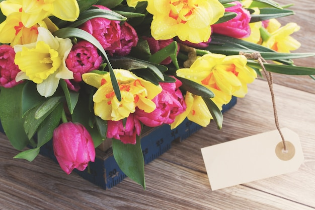 Frühlingstulpen und narzissenblumen mit leerem tag instagram retro filter