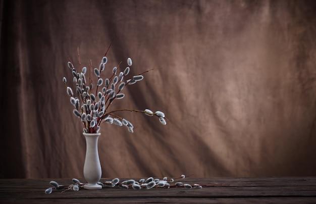 Frühlingsweidenzweige in der vase auf braunem dunklem hintergrund