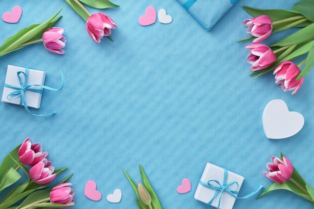 Frühlingswohnung lag mit geschenkboxen, rosa tulpen und dekorativen herzen, kopierraum