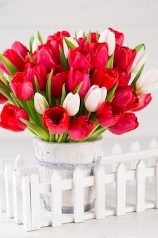 Frühlingszeit. roter tulpenstrauß auf dem weißen hölzernen hintergrund.