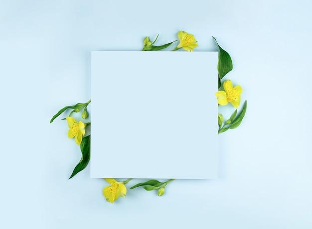 Frühlingszusammensetzung. gelbe blumen, papierrohling auf pastellblauem hintergrund. flache lage, draufsicht, kopierraum, modell.