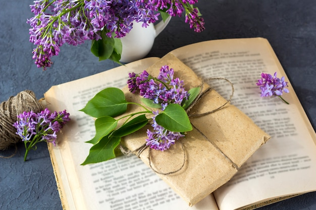 Frühlingszusammensetzung. hübsche geschenkbox, eingewickelt mit braunem bastelpapier und verziert mit einem bündel flieder liegt auf einem offenen buch auf dunklem hintergrund.