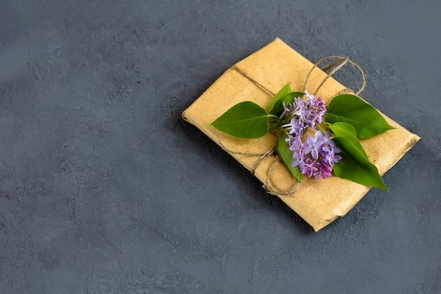 Frühlingszusammensetzung. hübsche geschenkbox, eingewickelt mit braunem bastelpapier und verziert mit fliederstrauß auf dunklem hintergrund. draufsicht, platz für text kopieren.