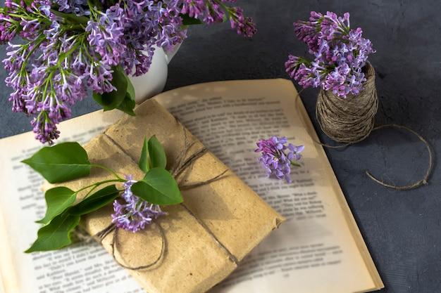 Frühlingszusammensetzung. hübsche geschenkbox mit braunem bastelpapier umwickelt und mit flieder verziert liegt auf einem offenen buch an einer dunklen wand. geschenkverpackungskonzept. draufsicht, nahaufnahme