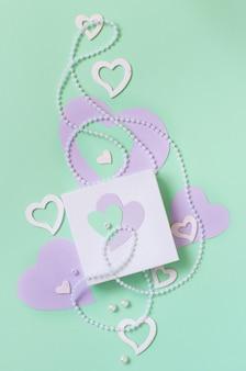 Frühlingszusammensetzung mit herzen und geschenkbox auf einem pastellhintergrund