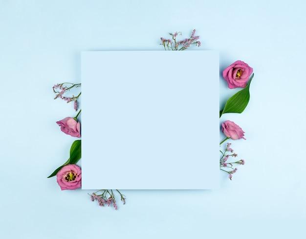 Frühlingszusammensetzung. rosa blumen, papierrohling auf pastellblauem hintergrund. flache lage, draufsicht, kopierraum, modell.