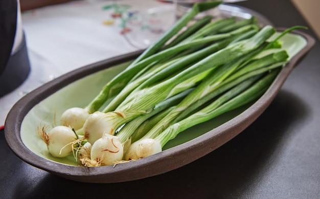 Frühlingszwiebeln im teller bereit zum kochen in der küche