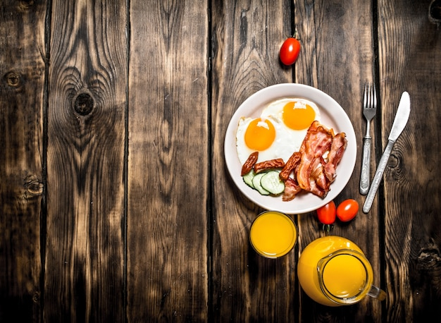 Frühstück am morgen. gebratener speck mit eiern und orangensaft. auf einem holztisch.