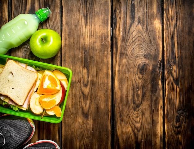 Frühstück am morgen. sandwiches, obst, milchshake und sportschuhe